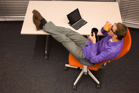 heaving: man sitting at with legs on the desk with thermal mug, heaving break in work eating hamburger in office Stock Photo