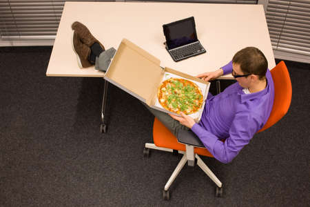 heaving: man sitting at with legs on the desk, heaving break pizza - fast meal in office