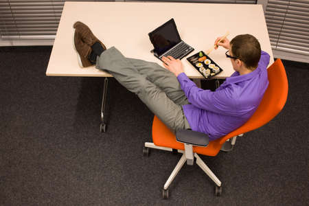 man sitting at with legs on the desk, working with tablet, eating sushi with chopsticks in office photo