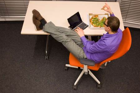 heaving: man sitting at with legs on the desk, heaving eating pizza, working on tablet Stock Photo