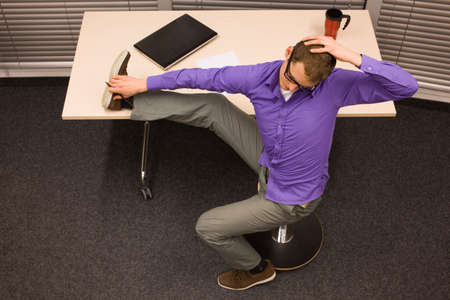 workplace wellness: short break for exercises in office at workplace