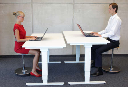 Business men and women working in correct sitting posture with laptops on pneumatic leaning seats at electric height adjustable desks in office Stock Photo
