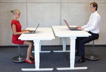 Hombres y mujeres de negocios que trabajan en la postura sentada correcta con los ordenadores portátiles en los asientos que se inclinan neumáticos a la altura eléctrica escritorios ajustables en la oficina