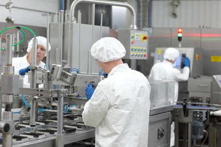 drei Arbeiter in weißen Schürzen, Mützen und Handschuhen in Produktionslinie im Werk