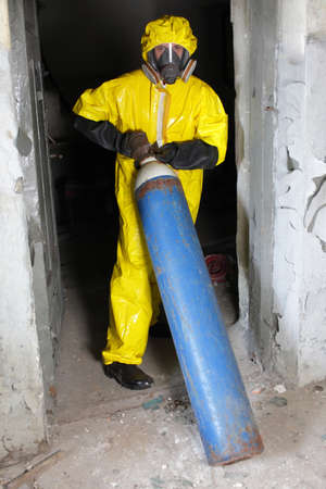 technician in yellow protective uniform, mask, and gloves dealing with steel cylinder with gas