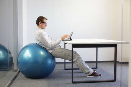 若い男がタブレット、デスクでの安定性のボールにリラックスの位置