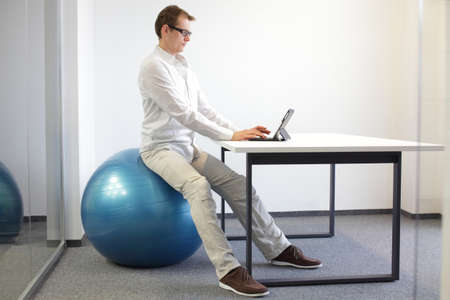 young man on stability ball at desk with tablet,proper  sitting posture