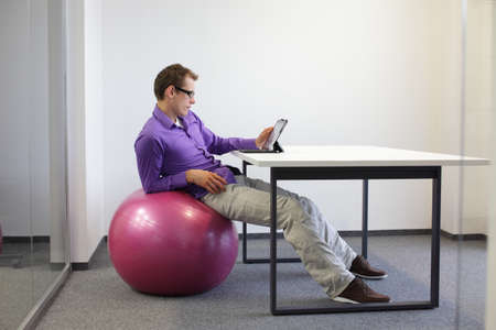human factors: young man on stability ball at desk with tablet,relaxed position Stock Photo