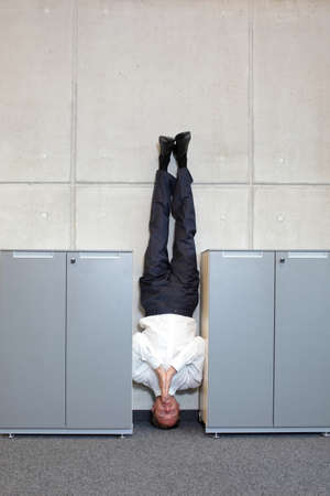 cabinets: business man standing on his head between cabinets in office Stock Photo