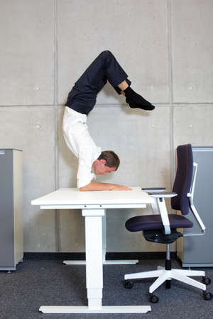 fit,flexible business man in scorpion asana on desk in his office