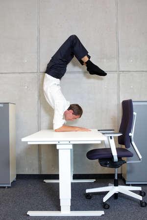 fit,flexible business man in scorpion asana on desk in his office