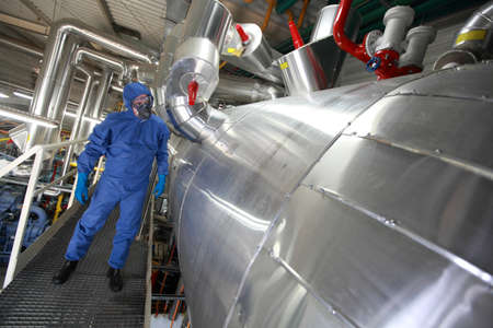 power failure: Technician  in mask,gloves,goggles and blue uniform checking technological system Stock Photo