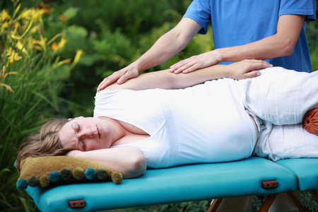reducing: Physical therapist massaging pregnant woman s arm - reducing stress - close up