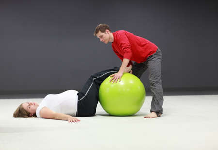 stability: pregnant woman and personal trainer with large stability ball training Stock Photo