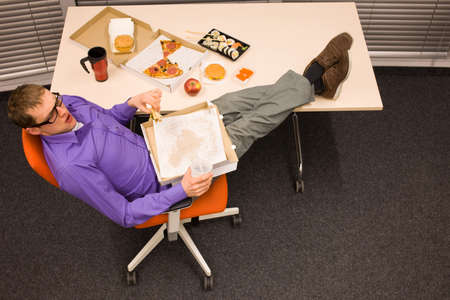 unhealthy: lunch in office - man sitting with feet on the table, suffering from overeating Stock Photo