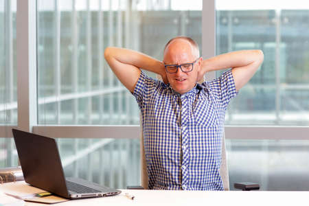 balding: middle age balding man with pain in the neck stretching arms in his office Stock Photo