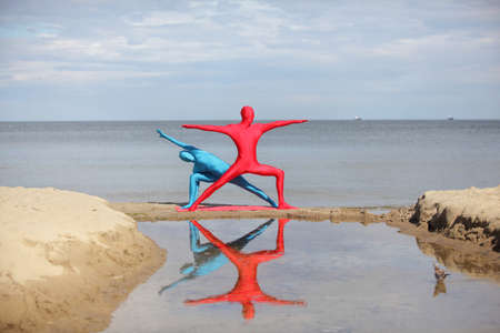 combines: yoga in kaleidoscope at the beach, couple in anonymous colorful costumes Stock Photo