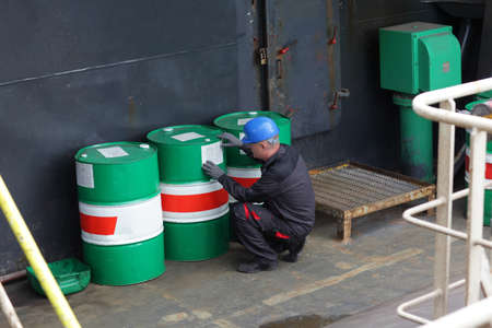 trabajador petroleros: Trabajador inspeccionar barriles industriales en planta industrial Foto de archivo