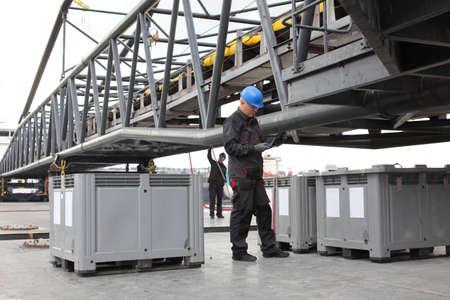 Werknemers in overtrekken en bouwvakker werken op industriële site.