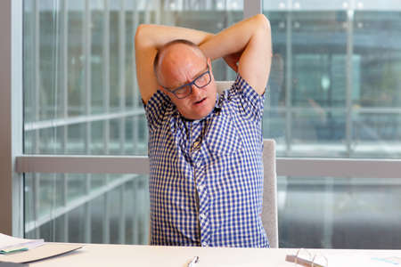 uptight: middle age balding man with pain in the neck stretching arms in his office Stock Photo