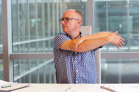 balding: middle age balding man  stretching arm in his office