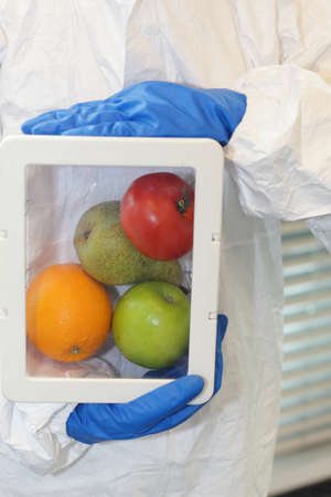 enhanced health: Scientist dressed in protective gear holding fruits and vegetables in plastic container - close up