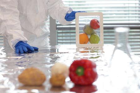 Científico vestido con equipo de protección que sostiene las frutas y verduras en un recipiente de plástico Foto de archivo