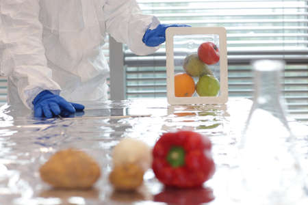 enhanced health: Scientist dressed in protective gear holding fruits and vegetables in plastic container