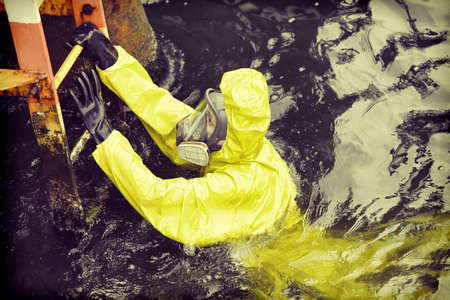 protective suit: worker in protective suit in sea reaching ladder to save his life