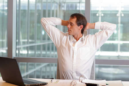 arm chair: white collar worker male stretching arms, relaxing neck - short break for exercise on chair in office