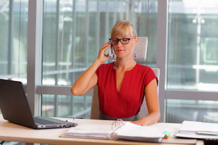 women sitting: caucasian business woman in eyeglasses on phone in her office Stock Photo