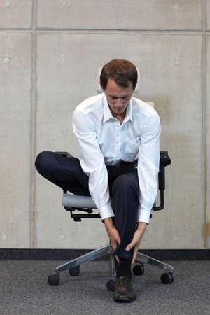 sillon: hombre de negocios que ejercita en la silla - la prevención de enfermedades ocupacionales oficina