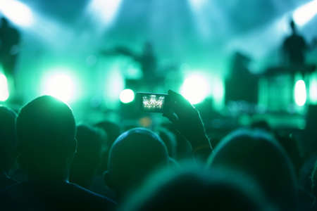 exhibition crowd: man in crowd with smart phone recording concert Stock Photo