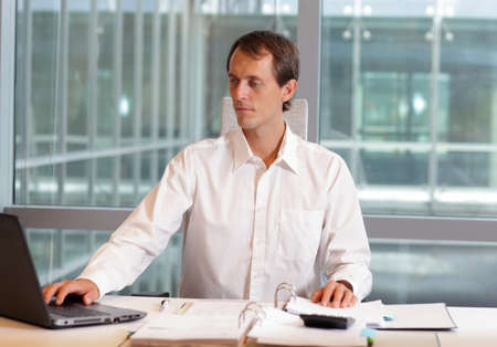 uptight: white collar worker caucasian male working with laptop in his office
