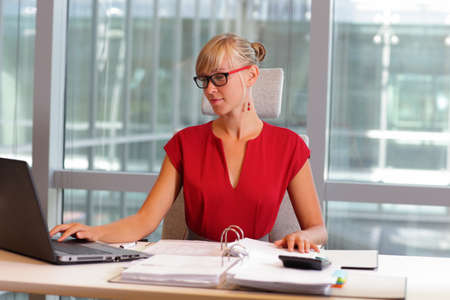 business woman working: caucasian business woman in eyeglasses working on laptop in her office