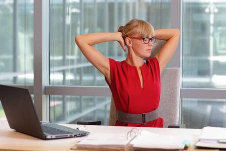 Kaukasische zakenvrouw in brillen ontspannen nek, stretching armen - korte pauze voor de oefening op de stoel in officecaucasian zakenvrouw in brillen ontspannen nek, stretching armen - korte pauze voor de oefening op de stoel in het kantoor