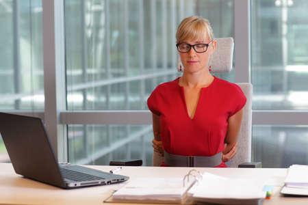 estiramiento: mujer de negocios caucásico en lentes de relax, que se remonta - breve descanso para hacer ejercicio en la silla en la oficina Foto de archivo