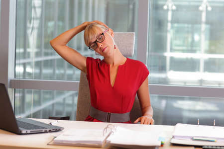 front desk: caucasian business woman in eyeglasses relaxing neck,stretching arms - short break for exercise on chair  in office