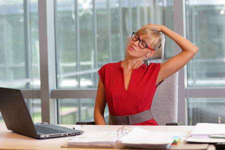 collo: caucasica donna d'affari in occhiali collo di relax, le braccia di stretching - breve vacanza per l'esercitazione sulla sedia in ufficio Archivio Fotografico