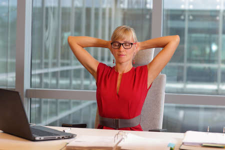 office break: caucasian business woman in eyeglasses relaxing neck,stretching arms - short break for exercise on chair  in office