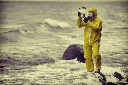 protective suit: Specialist in protective suit checking sample of water in container on rocky sea, ocean shore