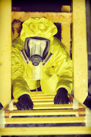 protective suit: overhead view of specialist in protective suit and mask  on ladder