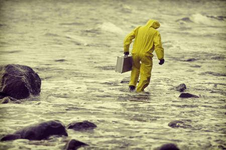 ecosistema: técnico en traje de protección con el caso de plata caminar en el agua en la playa rocosa - vista posterior