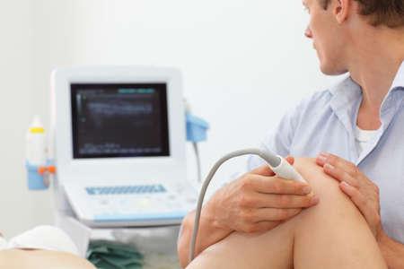 de rodillas: rodilla prueba dinámica conjunta del paciente femenino lleva a cabo con el uso de un ultrasonido