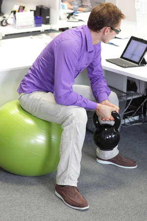 human factors: man on ball working out with kettlebell during offce work