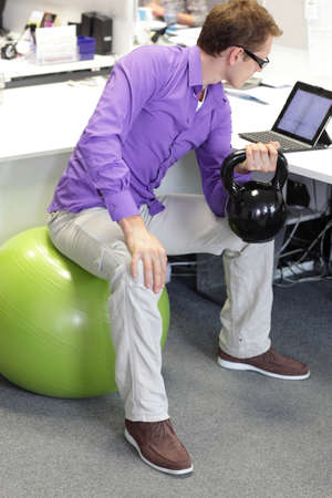 casual office: man on ball working out with kettlebell during offce work