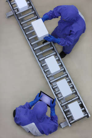 packs: overhead view of two workers in blue uniforms working with boxes on packing line