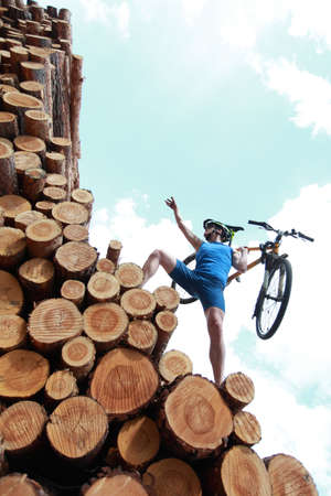 will power: fit man with his bicycle climbing on top of large pile of logs