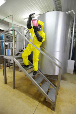 wellies: industrial professional , in protective uniform,mask,goggles,gloves and wellies checking sample in plastic container Stock Photo