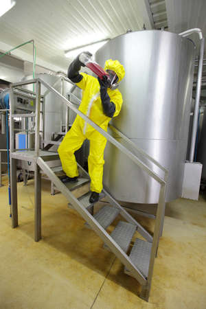 welly: industrial professional , in protective uniform,mask,goggles,gloves and wellies checking sample in plastic container Stock Photo